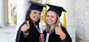 Smiling graduating students putting their thumbs up while looking at the camera